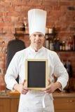 Szczęśliwy męski szef kuchni z pustą menu deską w kuchni Zdjęcie Royalty Free