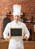 Szczęśliwy męski szef kuchni z pustą menu deską w kuchni Zdjęcie Stock