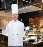 Szczęśliwy męski szefa kuchni kucharz z cloche pokazuje ok znaka Fotografia Royalty Free