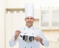 Szczęśliwy męski szefa kuchni kucharz z garnkiem i łyżką Fotografia Royalty Free