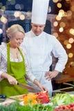Szczęśliwy męski szefa kuchni kucharz z kobiety kucharstwem w kuchni Obrazy Stock