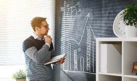 Szczęśliwy męski uczeń, nauczyciel, freelancer z kredą przy blackboard Zdjęcie Stock