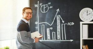 Szczęśliwy męski uczeń, nauczyciel, freelancer z kredą przy blackboard Fotografia Stock