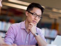 Szczęśliwy męski uczeń pracuje przy biblioteką Obraz Royalty Free