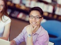 Szczęśliwy męski uczeń pracuje przy biblioteką Zdjęcia Stock