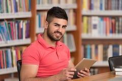 Szczęśliwy Męski uczeń Pracuje Z laptopem W bibliotece Zdjęcie Stock