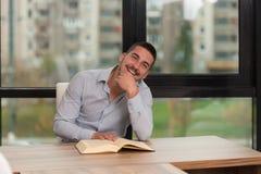 Szczęśliwy Męski uczeń W bibliotece Z książką Fotografia Stock
