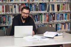 Szczęśliwy Męski uczeń Z laptopem W bibliotece Zdjęcia Royalty Free