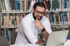 Szczęśliwy Męski uczeń Z laptopem W bibliotece Fotografia Stock