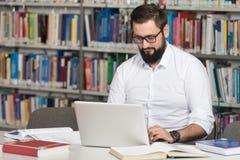 Szczęśliwy Męski uczeń Z laptopem W bibliotece Obrazy Stock