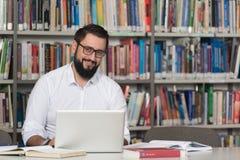 Szczęśliwy Męski uczeń Z laptopem W bibliotece Zdjęcie Stock