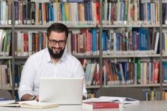 Szczęśliwy Męski uczeń Z laptopem W bibliotece Obraz Stock