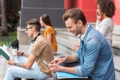 Szczęśliwy męski uczeń zabawia z gadżetem blisko uniwersyteckiego budynku Zdjęcie Stock