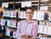 Szczęśliwy męskiego ucznia mienie rezerwuje przy biblioteką Fotografia Stock