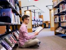 Szczęśliwy męskiego ucznia mienie rezerwuje przy biblioteką Obraz Stock