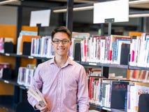 Szczęśliwy męskiego ucznia mienie rezerwuje przy biblioteką Obrazy Royalty Free