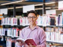 Szczęśliwy męskiego ucznia mienie rezerwuje przy biblioteką Zdjęcia Stock