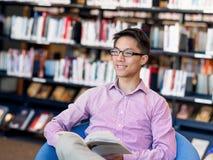 Szczęśliwy męskiego ucznia mienie rezerwuje przy biblioteką Zdjęcie Royalty Free