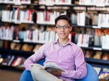 Szczęśliwy męskiego ucznia mienie rezerwuje przy biblioteką Zdjęcia Royalty Free