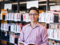 Szczęśliwy męskiego ucznia mienie rezerwuje przy biblioteką Obrazy Stock