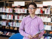 Szczęśliwy męskiego ucznia mienie rezerwuje przy biblioteką Obraz Royalty Free