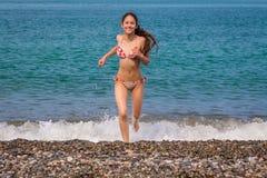 Szczęśliwy młoda dziewczyna bieg od morza Obrazy Royalty Free
