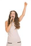 Szczęśliwy młoda kobieta śpiew z mikrofonem fotografia stock