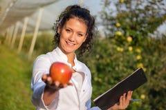 Szczęśliwy młoda kobieta agronom z czerwonym jabłkiem w jej ręce Fotografia Stock