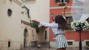 Szczęśliwy młoda kobieta taniec i mieć zabawa z parasolem na ulicie stary miasto Piękny firl patrzeje i pozuje zbiory