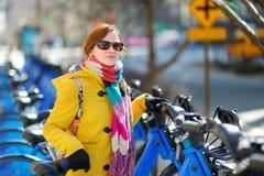 Szczęśliwy młoda kobieta turysta gotowy jechać do wynajęcia bicykl w Miasto Nowy Jork przy pogodnym wiosna dniem Żeński podróżnik obraz stock