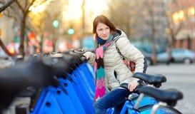 Szczęśliwy młoda kobieta turysta gotowy jechać do wynajęcia bicykl w Miasto Nowy Jork przy pogodnym wiosna dniem Żeński podróżnik fotografia stock