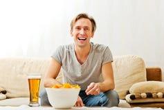 Szczęśliwy młodego człowieka dopatrywanie bawi się na TV zdjęcie stock