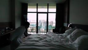 Szczęśliwy młodego człowieka doskakiwanie na łóżku przy hotelem w bathrobe zdjęcie wideo