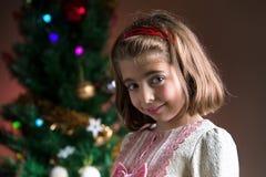 Szczęśliwy młodej dziewczyny czekania bożych narodzeń prezent pod drzewem w domu Zdjęcie Stock