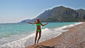 Szczęśliwy młodej dziewczyny doskakiwanie na plaży swobodny ruch zbiory