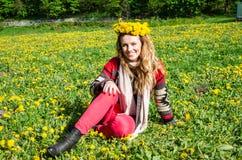 Szczęśliwy młodej dziewczyny obsiadanie w parku na polu trawa i dandelions z bukietem dandelions na jego głowa i ono uśmiecha się Fotografia Stock
