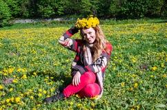 Szczęśliwy młodej dziewczyny obsiadanie w parku na polu trawa i dandelions z bukietem dandelions na jego głowa i ono uśmiecha się Obrazy Royalty Free