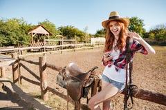 Szczęśliwy młodej kobiety cowgirl z telefonem komórkowym pokazuje pokoju znaka Zdjęcie Stock