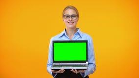 Szczęśliwy młodej kobiety mienia laptop z zieleń ekranem, początkowa prezentacja, app zdjęcie wideo