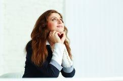 Szczęśliwy młodej kobiety obsiadanie przy przyglądającym up i stołem Zdjęcia Stock