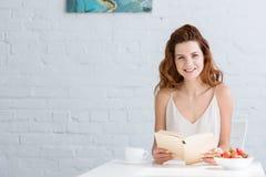 szczęśliwy młodej kobiety obsiadanie przy stołem z kawą i książką truskawkową i czytelniczą fotografia royalty free
