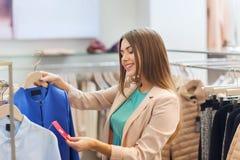 Szczęśliwy młodej kobiety wybierać odziewa w centrum handlowym Fotografia Stock