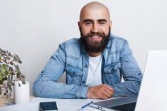 Szczęśliwy młody łysy biznesmen ma gęstą ciemną brodę ubierającą w cajgowej koszula siiting przy stołem w jego biurze z laptopem  zdjęcie royalty free