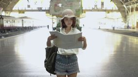 Szczęśliwy młody żeński kierunek i patrzeć na lokaci mapie przy dworcem przed podróżą zbiory wideo