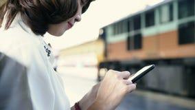 Szczęśliwy młody żeński obsiadanie na ławce używać smartphone dla opowiadać, czytać i texting, przy dworcem zbiory wideo