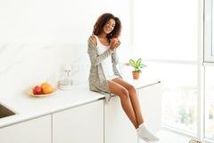 Szczęśliwy młody afro amerykański kobiety obsiadanie na kuchennym stole Obraz Royalty Free