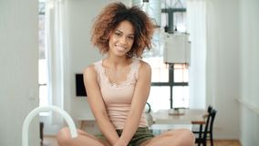 Szczęśliwy młody afro amxerican kobiety obsiadanie na kuchennym stole w domu Zdjęcie Stock
