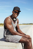 Szczęśliwy młody afrykański mężczyzna obsiadanie na deptaku Fotografia Royalty Free