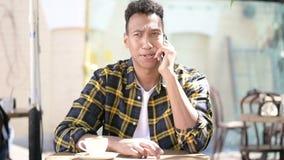 Szczęśliwy młody afrykański mężczyzna opowiada na telefonie, plenerowa kawiarnia zbiory