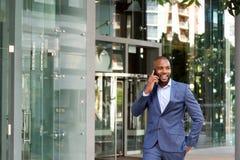 Szczęśliwy młody amerykanina afrykańskiego pochodzenia biznesmen opowiada na telefonie komórkowym Fotografia Royalty Free